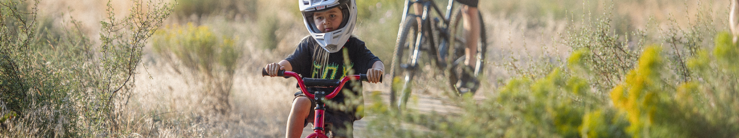 Young rider pedals through the fields on a bike wearing a Fox Racing tee
